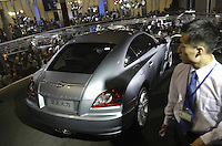 A man looks at a Chrysler Crossfire at the Auto China 2004 exhibition in Beijing, China..