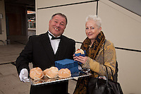 Pictured handing out free bacon butties to promote East Midlands Trains complimentary breakfast for First Class passengers is singing butler Alberto and Derby passenger Ann Muirhead