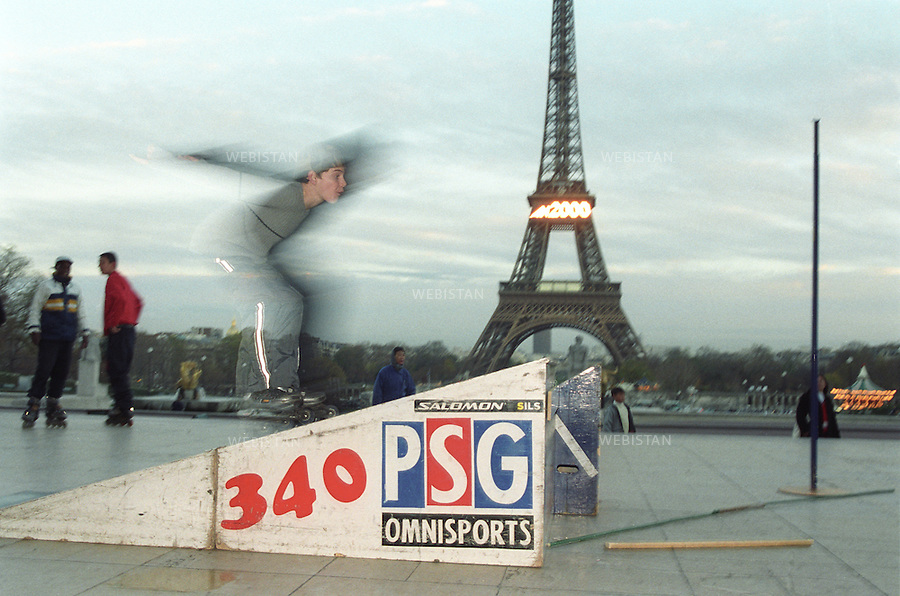 2000. France. Paris. Eiffel Tower.Teenager with roller skates jumping from a springboard with the Eiffel Tower on the backside. France. Paris. Tour Eiffel. Adolescent en rollers sautant depuis un tremplin avec la tour Eiffel au fond.