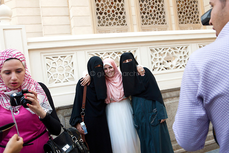 Egypt / Cairo / 14.7.2012 / Manar, a Sister, takes pictures with two friends following her wedding in El Rahman El Rahim Mosque, in Abbasseya, Cairo, Egypt. July 14th, 2012.<br /> <br /> © Giulia Marchi