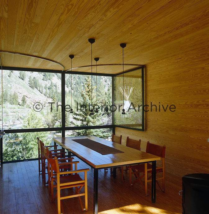 The dining room walls are lined with untreated wood and the large windows open on rails enabling the view to become part of the room