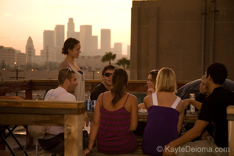 A group of young men and women gathered on the top of the Brewery Arts Complex in Downtown Los Angeles at sunset with the downtown Los Angeles skyline in the background
