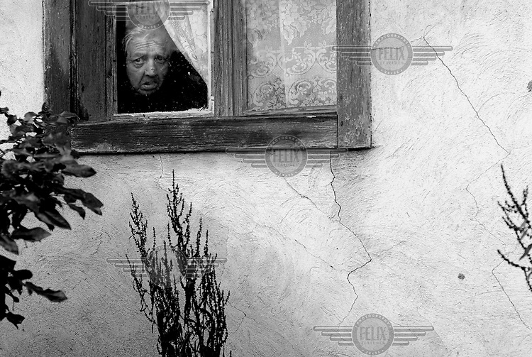 An elderly woman dressed in black widow clothing, looks through the window of her house in Bistrita.