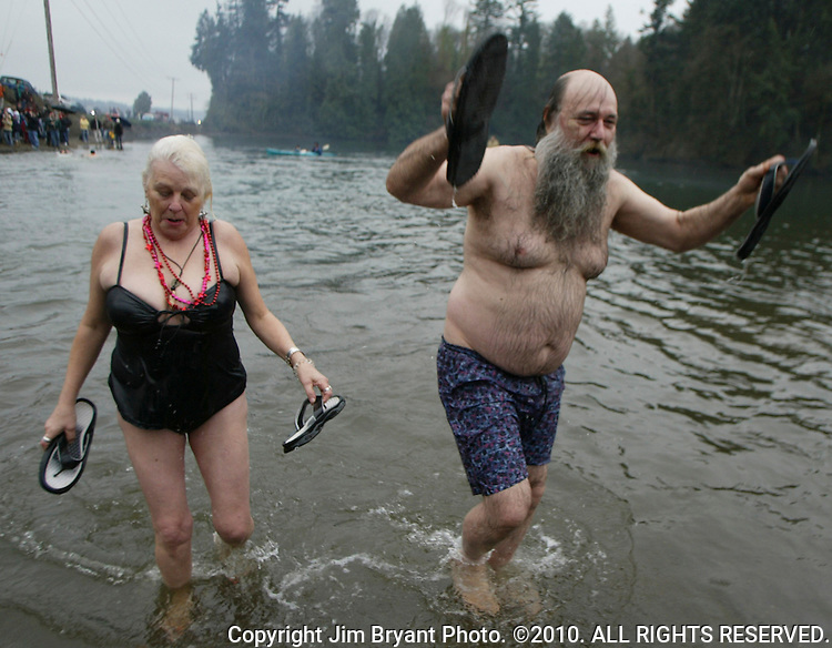 Linda Moore, left, and Jon Forseth get out of the water after participating in the 23rd annual Olalla polar bear jump into the Burley lagoon in Olallar, Washington on January 1, 2007.Jim Bryant Photo. ©2010. ALL RIGHTS RESERVED.