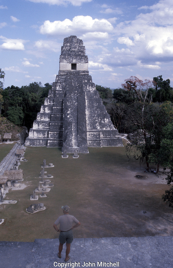 Tourist surveying the Great Plaza and Temple I, or Temple of the Grand Jaguar, from the top of Temple II, Tikal, Guatemala