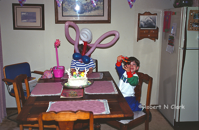 Boy and girl with balloon hats and Easter cake
