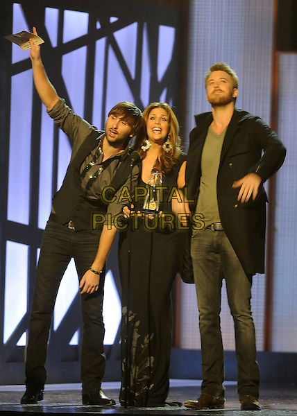 LADY ANTEBELLUM - Charles Kelley, Hillary Scott, and Dave Haywood .performs during the 43rd Annual CMA Awards, Country Music's Biggest Night, held at the Sommet Center, Nashville, Tennessee, USA, 11th November 2009. live show on stage full length arm raised up award winners winning microphone black dress speech accepting .CAP/ADM/LF.©Laura Farr/AdMedia/Capital Pictures.