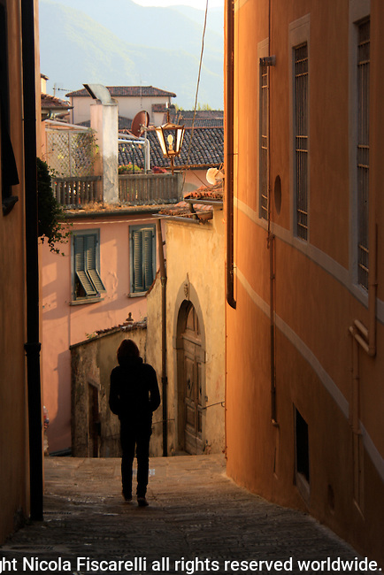 A young man walks in the narrow street of medieval hilltop town of Barga Tuscany.