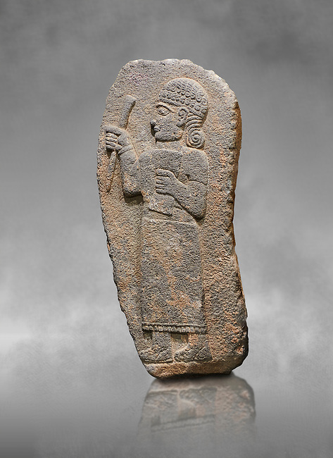 Hittite monumental relief sculpture of a figure holding a document. Adana Archaeology Museum, Turkey. Against a grey art background