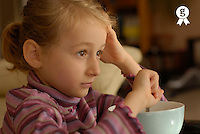 Girl (5-7) watching TV during breakfast, close-up, side view (Licence this image exclusively with Getty: http://www.gettyimages.com/detail/200502998-001 )