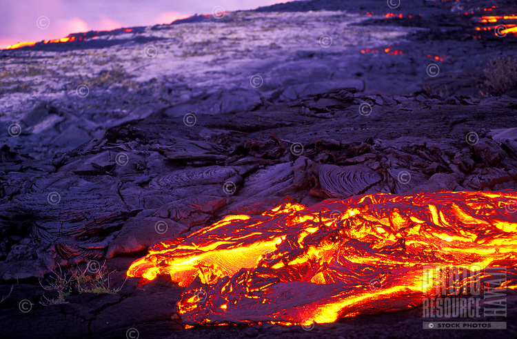 Glowing lava flows on its way to the sea.