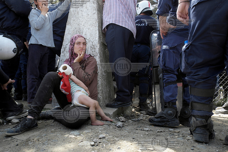 A refugee woman with her child sits near the Greek-Macedonian border fence as scuffles take place between migrants and police. About 40 people, mainly men, were demanding that the borders be opened after they were closed by the Macedonians. The Greek authorities have since closed the makeshift refugee camp at Idomeni, where the protestors were living, and distributed the occupants among several official camps around the country.