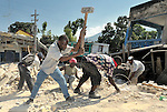 Men in earthquake-ravaged Port-au-Prince dig into the rubble of a building, hoping to find the remains of 20 people they believe are buried inside. The country was wracked by a devastating quake on January 12 that killed at least 150,000 and left hundreds of thousands homeless.