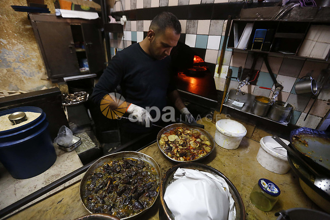 A Palestinian man cooks foods in a traditional oven during the holy fasting month of Ramadan, in the West Bank city of Hebron, on May 24, 2018. Photo by Wisam Hashlamoun