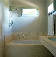 The bath and wash basin in this small contemporary bathroom are lined with stone