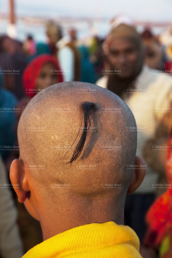 India. Uttar Pradesh state. Allahabad. Maha Kumbh Mela. An Indian Hindu devotee has shaved his head and left only a strand of hair. He has already taken a holy dip at Sangam. The Kumbh Mela, believed to be the largest religious gathering is held every 12 years on the banks of the 'Sangam'- the confluence of the holy rivers Ganga, Yamuna and the mythical Saraswati. In 2013, it is estimated that nearly 80 million devotees took a bath in the water of the holy river Ganges. The belief is that bathing and taking a holy dip will wash and free one from all the past sins, get salvation and paves the way for Moksha (meaning liberation from the cycle of Life, Death and Rebirth). Bathing in the holy waters of Ganga is believed to be most auspicious at the time of Kumbh Mela, because the water is charged with positive healing effects and enhanced with electromagnetic radiations of the Sun, Moon and Jupiter. The Maha (great) Kumbh Mela, which comes after 12 Purna Kumbh Mela, or 144 years, is always held at Allahabad. Uttar Pradesh (abbreviated U.P.) is a state located in northern India. 9.02.13 © 2013 Didier Ruef