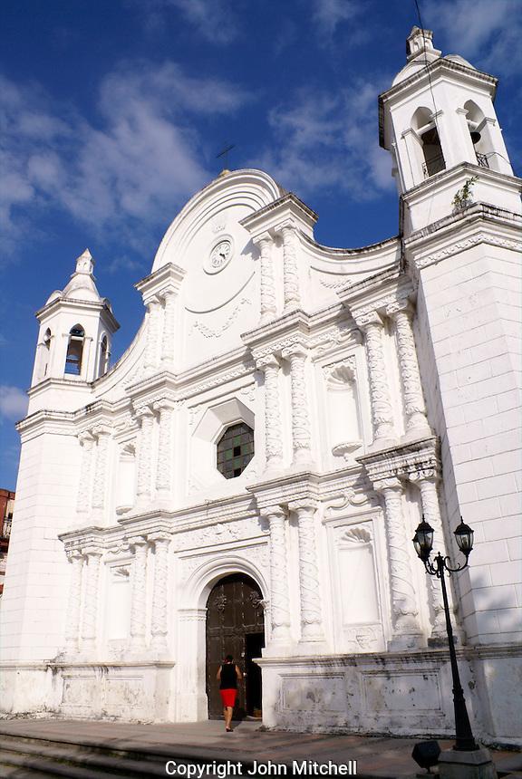 Woman entering Spanish colonial church facing the main plaza in Santa Rosa de Copan, Honduras.