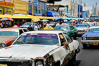 American classic cars from 1970s, used as a shared taxi, pass along the main road in Maracaibo, Venezuela, 10 May 2006.