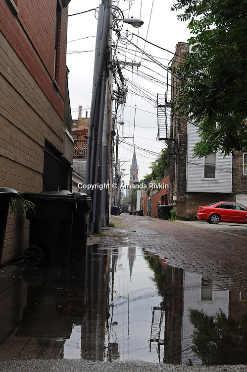 St. Michael's Church in Old Town is seen reflected in a puddle of rain water sitting in an alley after a rainstorm in Chicago, Illinois on June 19, 2009.