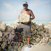 Albert Lentau's home has had to be moved inland as the sea started to erode the land around it. He has now collected coral rocks from the reef in the lagoon and builds an enclosure that he will fill with organic and inorganic waste, compact it then pile coral soil on top and thus reclaim the eroded land.