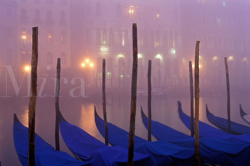 Italy, Venice. The Grand Canal with gondolas moored at dusk in the fog
