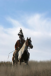 A Native American Indian man sitting bareback on a horse in traditional Sioux Indian clothing holding a stone mallot in South Dakota