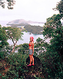 FIJI, Northern Lau Islands, a young woman stands on top of a lush uninhabited jungle island