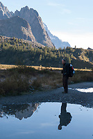 A hiker reflected in the still waters of Lac Combal along the Tour du Mont Blanc, September 2007