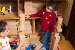 Education preschool 3-4 year old girl and boy in block area building matching towers, girl looking at boy's construction after building hers