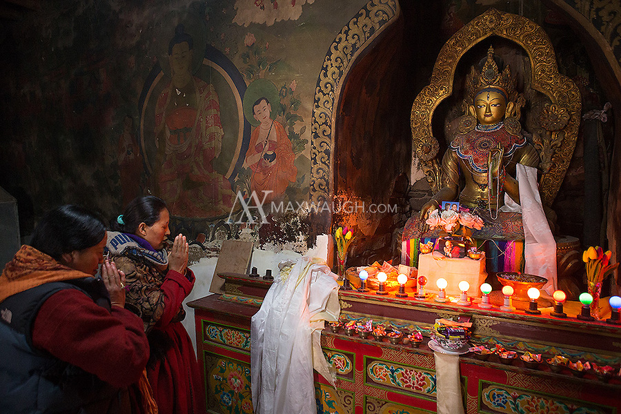 Women pray at an altar in the Hemis Monastery.
