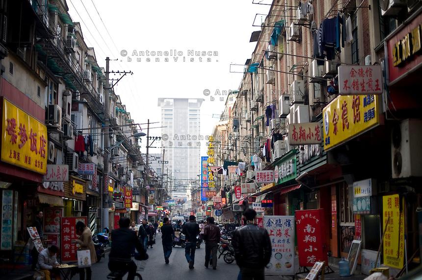 Una strada di un quartiere popolare di Shanghai.<br /> People walking on a street Old Town