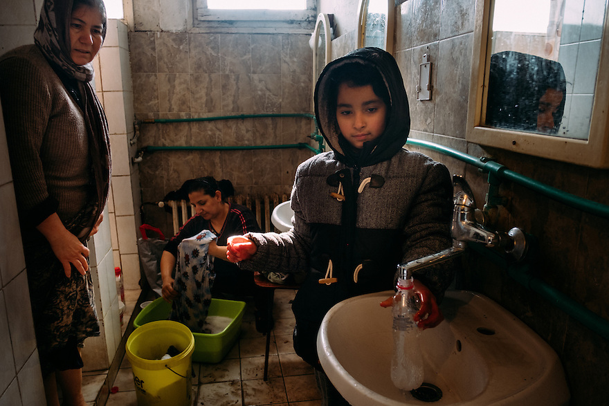 Yezidi women and girl doing laundry and chores in the dormitory bathrooms at Centre Krnjaca camp in Belgrade, Serbia which was hosting 1200 asylum-seekers, primarily families. In the past, the same camp hosted ethnic Serbs displaced from Bosnia and Kosovo.