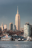 The Empire State Building contrasts against a post thunderstorm sky, with Chelsea Piers and other Chelsea buildings in the foreground and the Chrysler Building in the background.