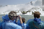 Niagara Falls, Ontario, Canada - 01 August 2006---Tourists / visitors equipped with blue plastic coats against the mist, during a cruise into the falls on the Niagara River---people---Photo: © HorstWagner.eu