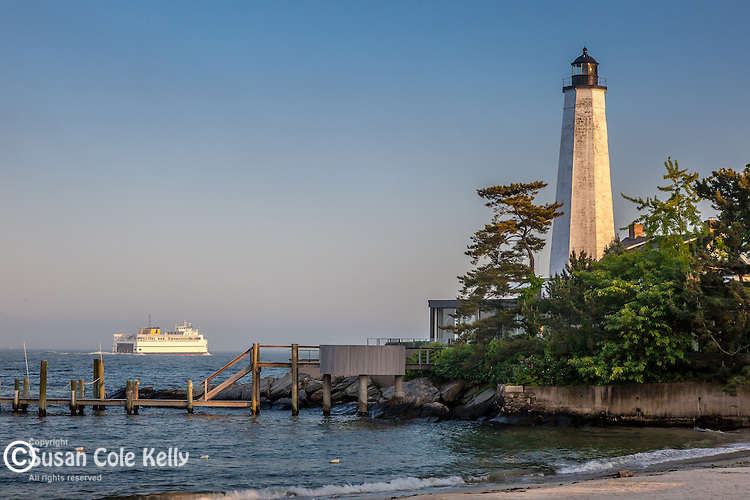 A ferry passes the New London Harbor Light, New London, CT, USA