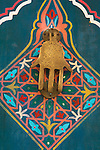 A painted door with a hamsa shaped knocker, Marrakesh, Morocco.