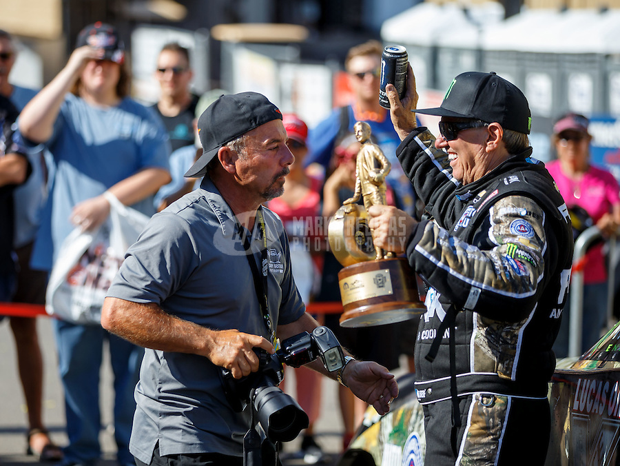 Jul 24, 2016; Morrison, CO, USA; NHRA funny car driver John Force celebrates with photographer Gary Nastase after winning the Mile High Nationals at Bandimere Speedway. Mandatory Credit: Mark J. Rebilas-USA TODAY Sports
