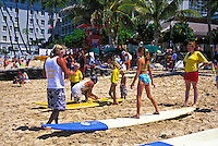 Young children on vacation are eager to learn surfing skills from an instructor on Waikiki Beach.