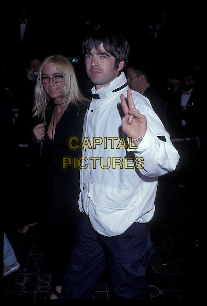 NOEL GALLANGHER & MEG MATHEWS.15 May 1996.Ref: 2535.peace sign, hand gesture, half length, half-length.*RAW SCAN- photo will be adjusted for publication*.www.capitalpictures.com.sales@capitalpictures.com.©Capital Pictures