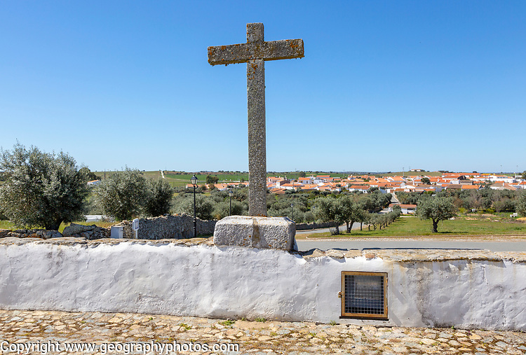 View of buildings rural country village from church Igreja Santa Bárbara de Padrões, near Castro Verde, Baixo Alentejo, Portugal, southern Europe overlooking olive trees and standing stone cross