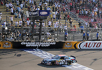 Oct. 10, 2009; Fontana, CA, USA; NASCAR Nationwide Series driver Joey Logano takes the checkered flag to win the Copart 300 at Auto Club Speedway. Mandatory Credit: Mark J. Rebilas-