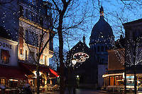 Place du Tertre and Sacré-Coeur Basilica, Paris, France. A low angle view of the Basilica, 1884-1914, designed by Paul Abadie, seen through the deserted Place du Tertre in the blue light of an early morning in winter. Built in white travertine on the top of the Butte de Montmartre, the Romano-Byzantine style Sacré-Coeur was designed as a monument to those who died in the Paris Commune during the Franco-Prussian War, 1870-71. Picture by Manuel Cohen