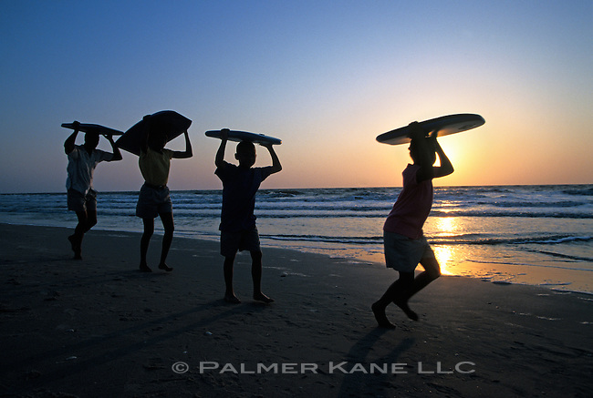 Family of Four Walking with Boggie Boards along Beach at Sunset