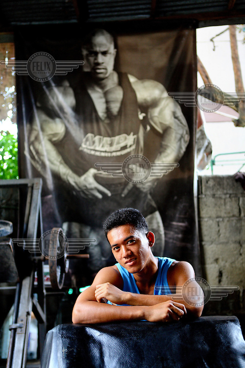 A man sits beneath a poster of a bodybuilder in a small gym.