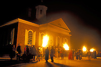 Colonial Williamsburg, Virginia, VA, Williamsburg, Illumination of Market Square at Christmas in front of the Courthouse in the evening in Colonial Williamsburg. Flickering cresset lights guide visitors through tours of historic buildings.
