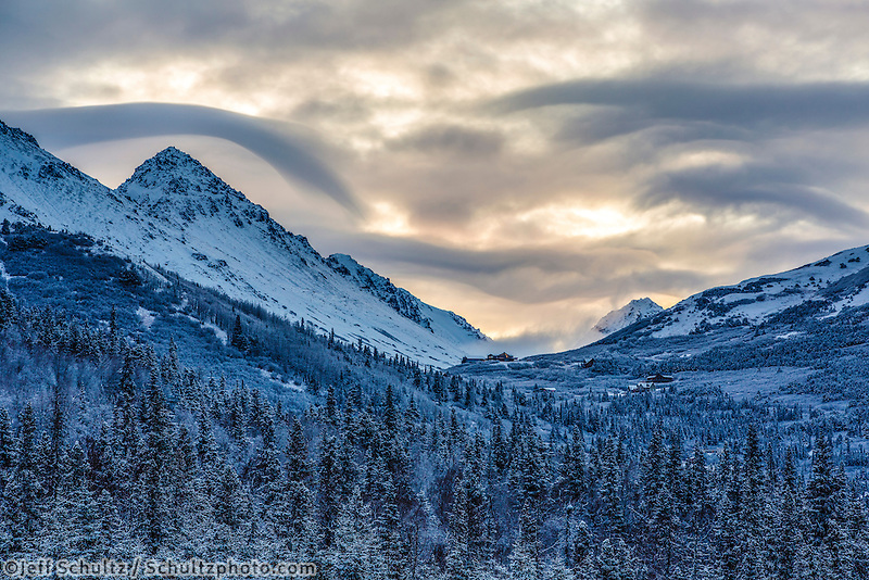 Winter landscape of sunrise and clouds over Chugach Mountains with snow covered forest in Anchorage, Alaska .  October 2015