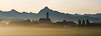 Wallfahrtskirche Maria Hilf  in the small village of Speiden with Early morning autumn mist and mountain peak Säuling in distance, Allgäu region, Bavaria, Germany