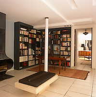 A modern living room with a tiled floor. A desk and chair are set in one corner in front of grey freestanding book cases.
