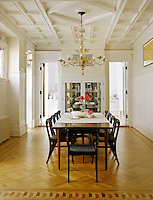 The elegant formal dining room with parquet flooring, a coffered ceiling and painted panelling