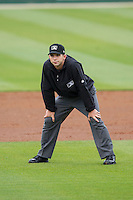 Umpire George Reidel handles the calls on the bases during the South Atlantic League game between the Greenville Drive and the Kannapolis Intimidators at CMC-Northeast Stadium on April 6, 2014 in Kannapolis, North Carolina.  The Intimidators defeated the Drive 8-5.  (Brian Westerholt/Four Seam Images)